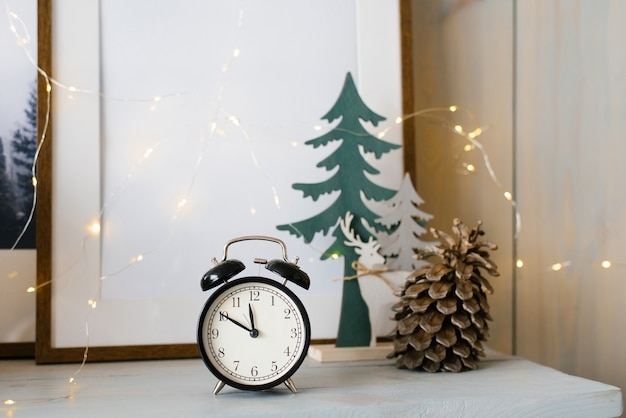 Black alarm clock and pine cone with lights