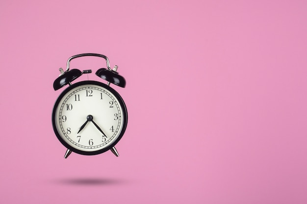 Black alarm clock on a pink background. creative composition.