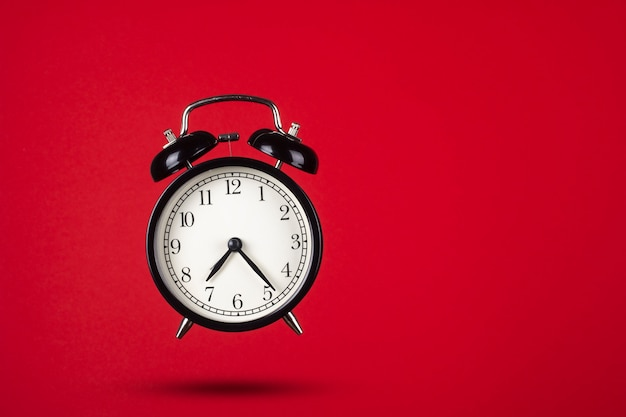 Black alarm clock on a red background. creative composition.