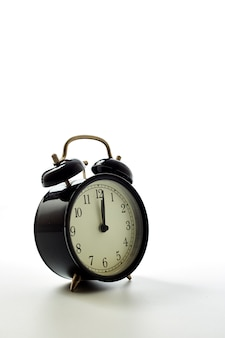 Black alarm clock retro style on white background