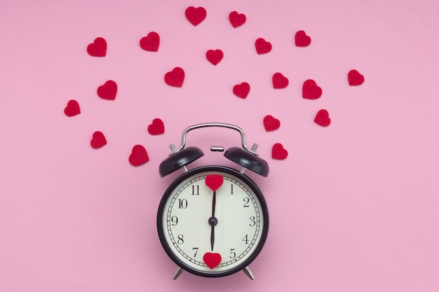 Black alarm clock in retro style with hearts instead of numbers and around in red small hearts