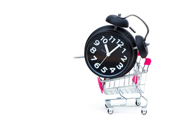 Black alarm clock and shopping cart or supermarket trolley