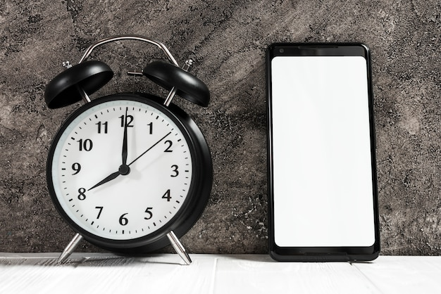 Black alarm clock and smartphone with white blank screen on desk against concrete black wall