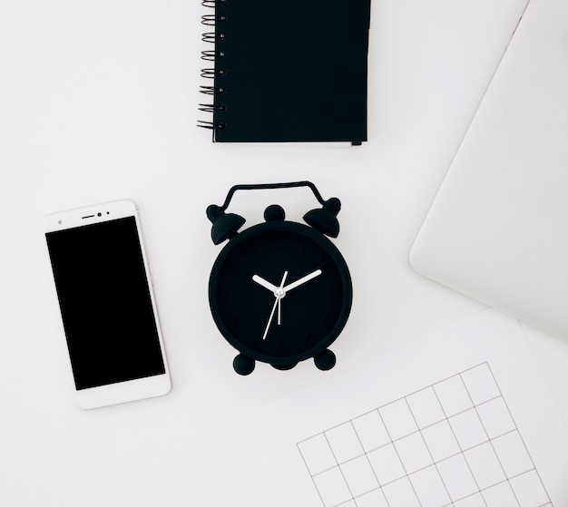 Black alarm clock; spiral notepad; smartphone; page and laptop on white desk