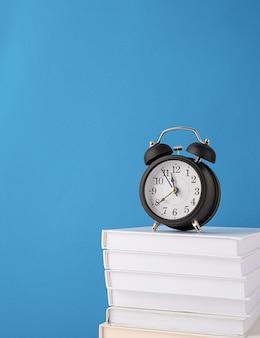 Black alarm clock on stack of books on blue background mockup design