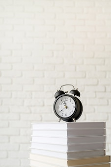 Black alarm clock on stack of books on white brick wall background