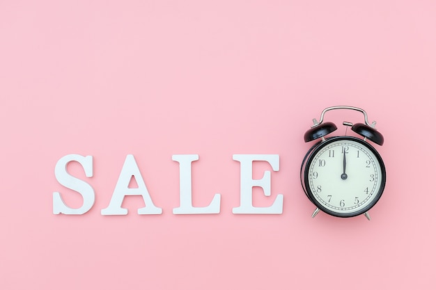Black alarm clock and text sale from white volume letters on pink