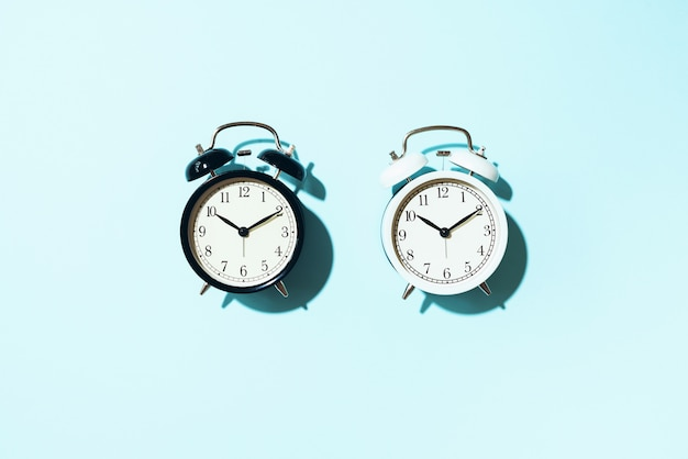 Black alarm clock and white one with hard shadow on blue background.