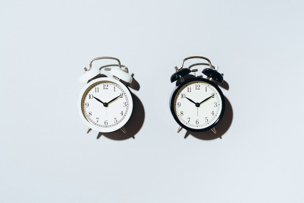 Black alarm clock and white one with hard shadow on grey background.