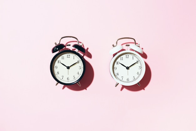 Black alarm clock and white one with hard shadow on pink background.