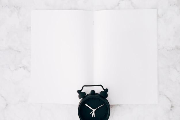 Black alarm clock over the white page against marble textured backdrop
