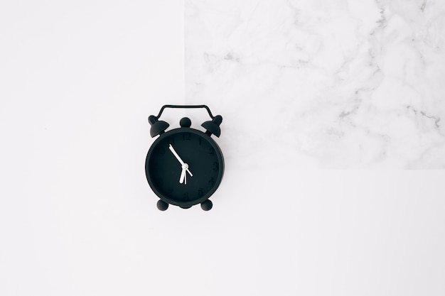 Black alarm clock on white texture background