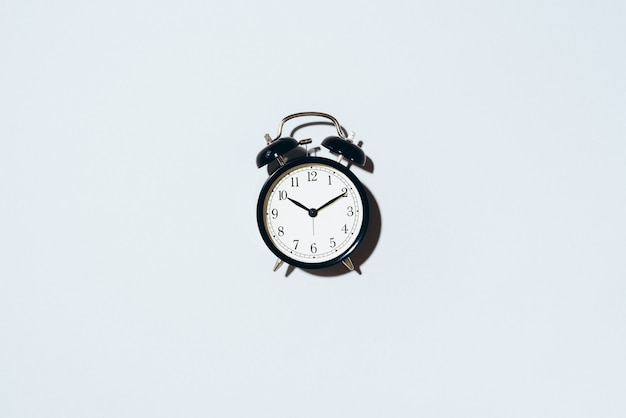 Black alarm clock with hard shadow on grey background.