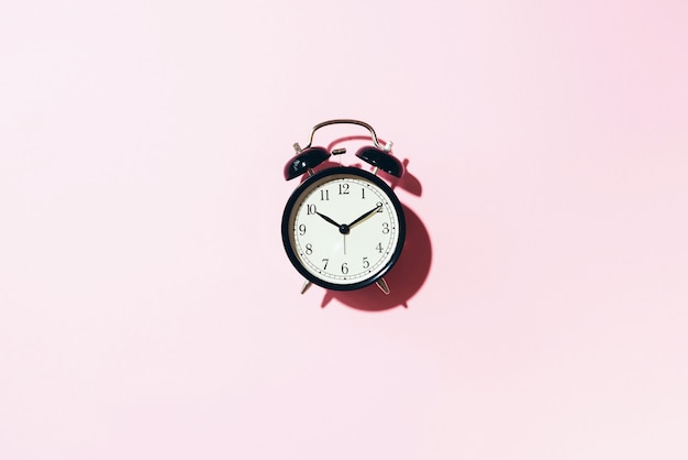 Black alarm clock with hard shadow on pink background.
