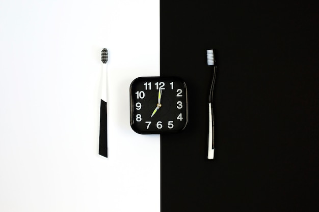 Black alarm clock with manual toothbrush set on white and black.