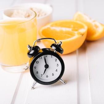 Black alarm clock with orange juice in glass on table
