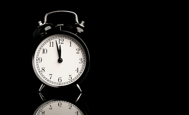 Черный будильник с отражением на черном фоне и копией пространства.