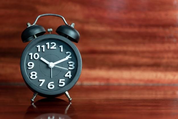 Black alarm clock on wooden floor.
