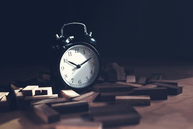 木製ブロックのスタックで黒い目覚まし時計