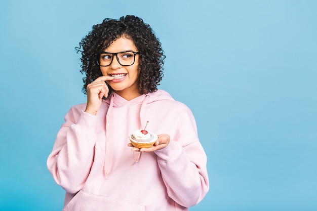 巻き毛のアフロヘアスタイルで黒人のアメリカ人のアフリカの幸せな女性は、青い背景の上に巨大な派手なデザートを食べて混乱しています。カップケーキを食べる。