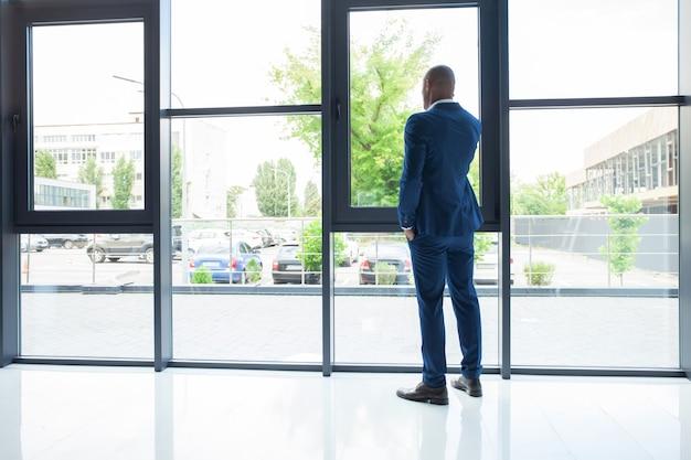 흑인 미국 사업가가 현대 사무실의 창가에 서서 휴대전화로 누군가에게 전화를 걸고 있습니다.