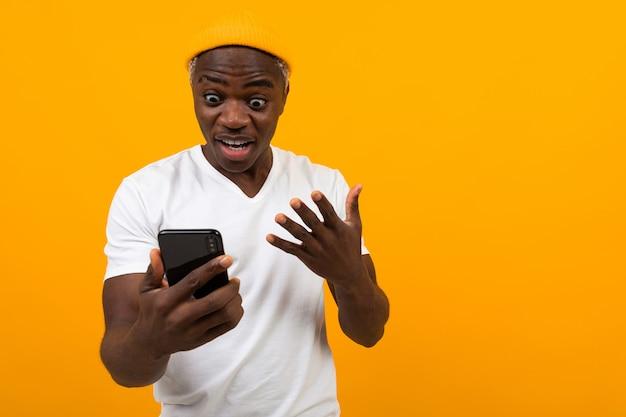 黒のアメリカ人男性がオレンジ色の電話で驚きに見える