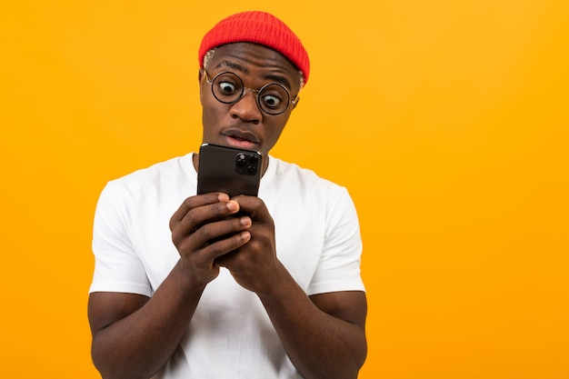 Black american man looks in surprise on the phone on yellow