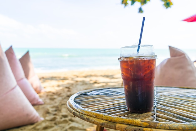 Черный стакан кофе американо на фоне моря