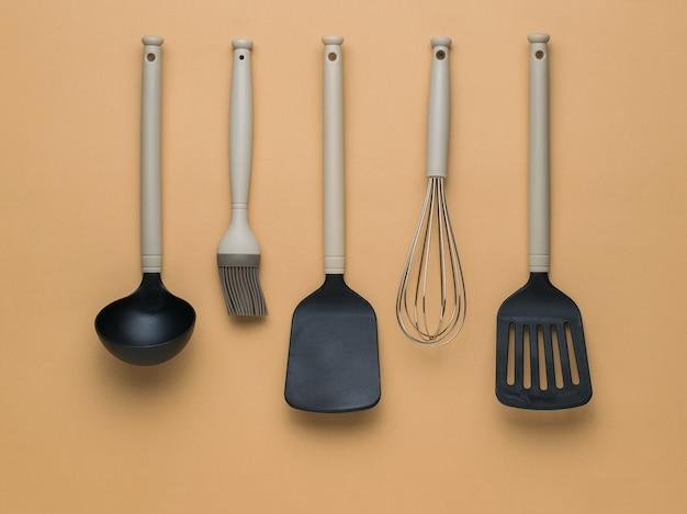 Черные и бежевые кухонные аксессуары на коричневом фоне. плоская планировка.