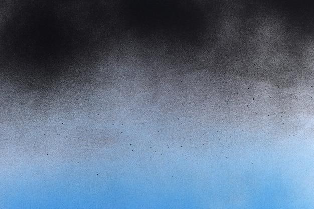 白い紙に黒と青のスプレーペイント
