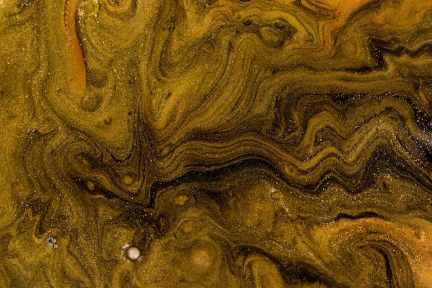 黒とゴールドの混合インクは、背景を波紋します。