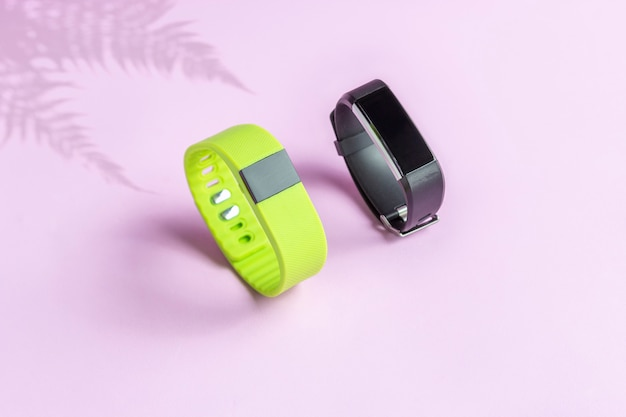 光の壁にシダの影を持つ黒と緑のフィットネス健康時計。