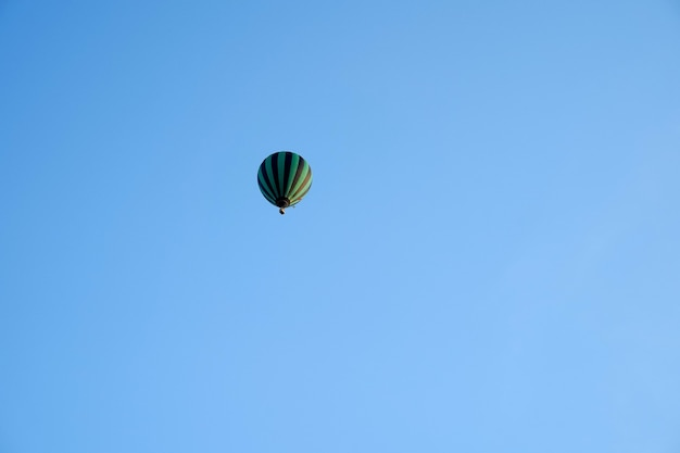 Черно-зеленый воздушный шар высоко в голубом небе