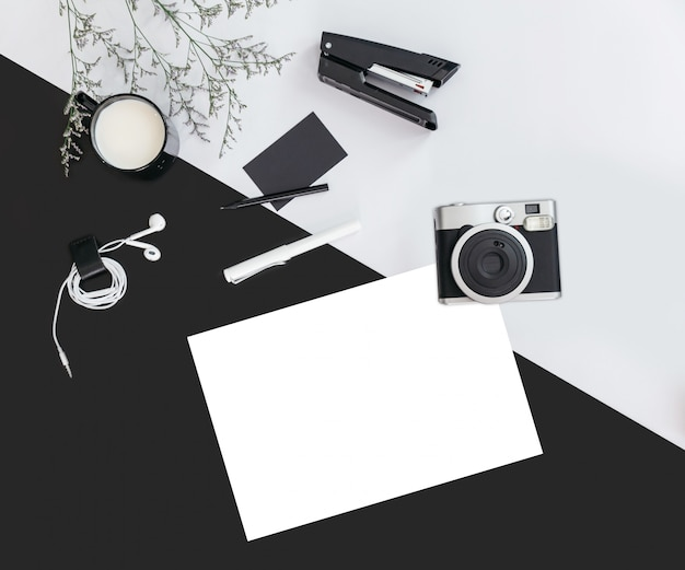 花の枝、一杯の牛乳、イヤホン、ペン、ホッチキス、カメラ、ネームカード、ホワイトペーパーの黒とグレーの色の背景。トップビューフレイレイ