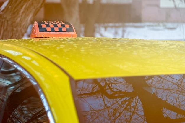 黄色いタクシーの車の屋根に黒とオレンジのタクシーの看板。ビューを閉じます。