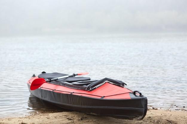 Черно-красное каноэ на песчаном берегу реки
