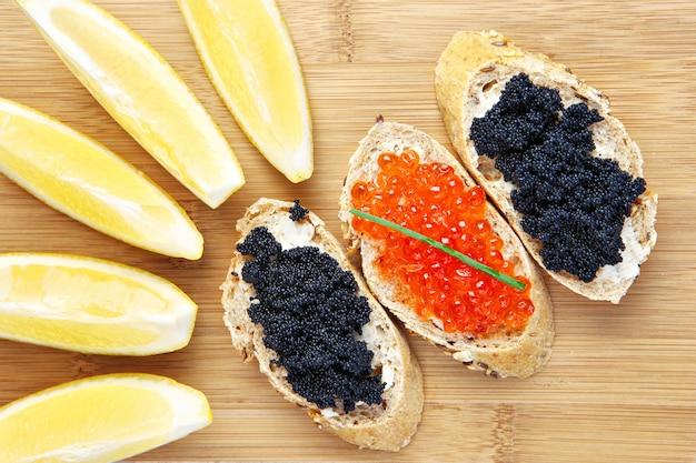 Бутерброды с черной и красной икрой с лимоном на деревянной доске