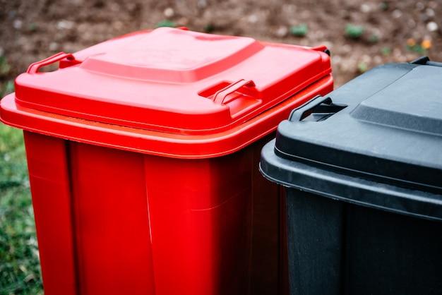 ガラス、プラスチック、紙、家庭ごみを分別・分別するための黒と赤のごみ容器。環境にやさしいごみ収集のコンセプトであるごみの分別。
