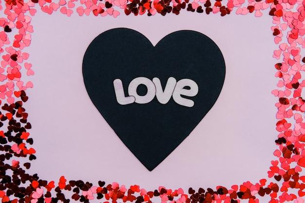 발렌타인 데이에 분홍색 배경에 단어 사랑 검정과 빨강 하트.