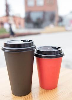 카페 밖에 있는 나무 테이블에 테이크아웃할 수 있는 검은색과 빨간색 종이컵. 아침에 방송되는 아침식사