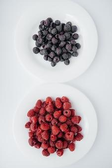 白い壁に黒と赤のラズベリーのクローズアップ。健康食品、天然ビタミン。新鮮なベリー。