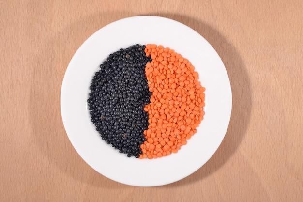 하얀 접시에 검정과 빨강 생 렌즈콩