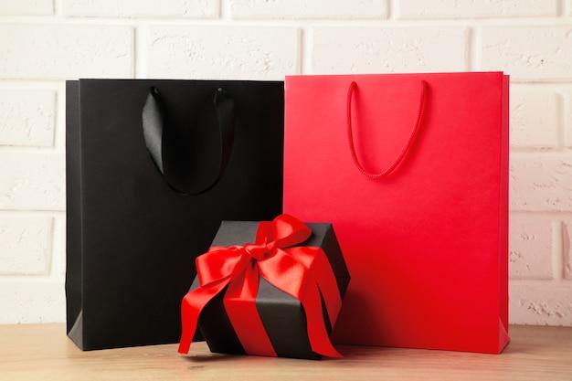 Черные и красные хозяйственные сумки с подарком на светлом фоне. черная пятница. вид сверху