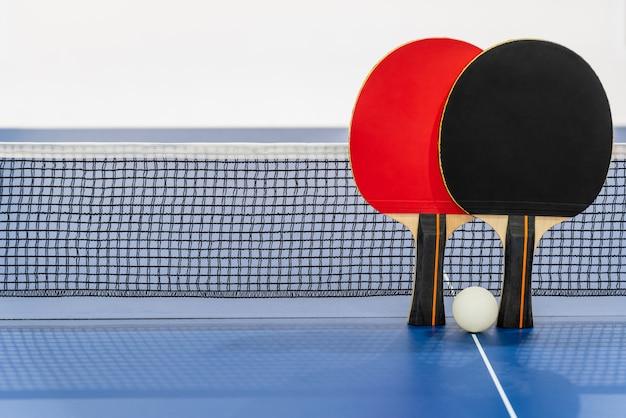 검은색과 빨간색 탁구 라켓과 그물이 있는 파란색 탁구대에 있는 흰색 공, 두 개의 탁구 패들은 스포츠 경기 장비 실내 활동 및 배경 개념을 위한 운동입니다.