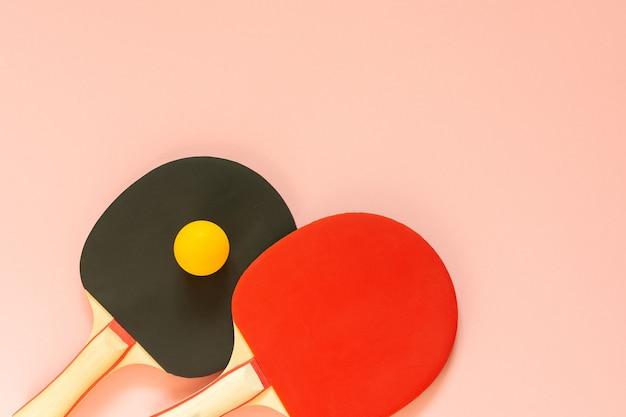 분홍색 배경에 격리된 검정 및 빨강 테니스 탁구 라켓과 주황색 공, 탁구용 스포츠 장비