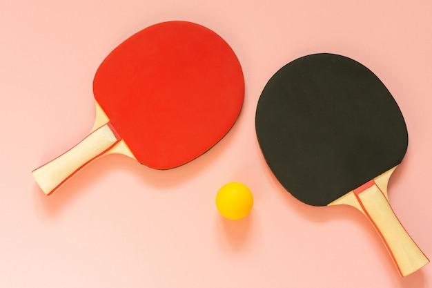 검정과 빨강 테니스 탁구 라켓과 분홍색 배경에 고립 된 오렌지 공 프리미엄 사진