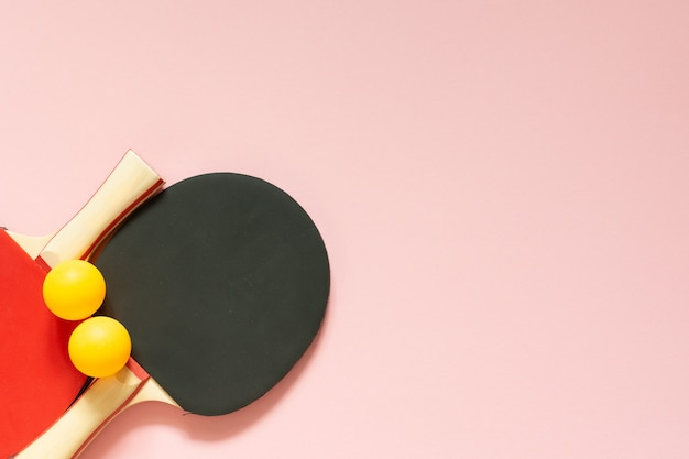검정과 빨강 테니스 탁구 라켓과 오렌지 공은 분홍색 배경에 고립, 탁구 스포츠 장비