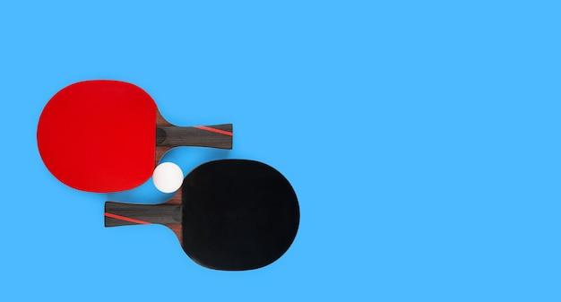 Черные и красные теннисные ракетки с мячом на синем столе