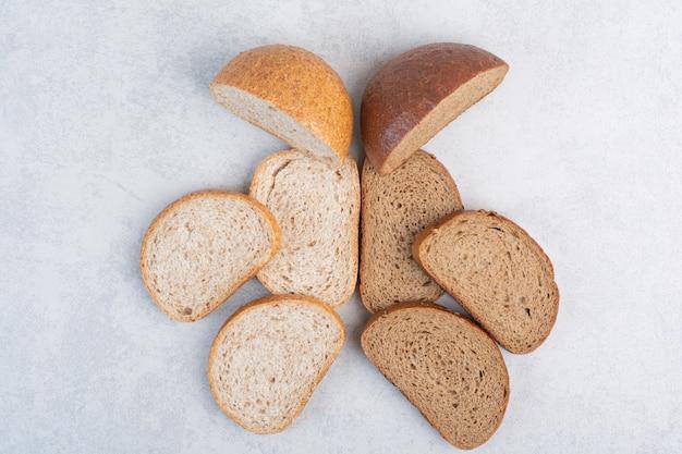 Ломтики черного и ржаного хлеба на каменной поверхности