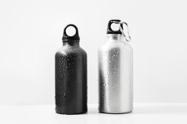 검정색과 은색, 재사용 가능한 알루미늄 보온병에 물을 뿌림